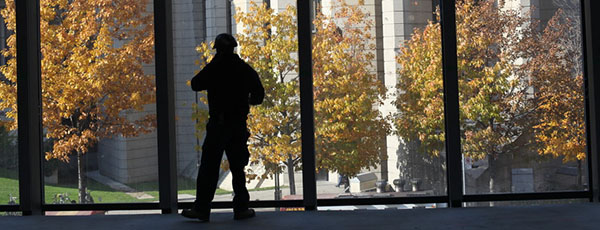 Photo of student silhouetted against fall foliage